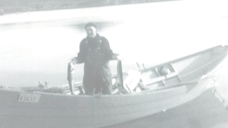 Pop holding a couple of salmon in his dory in Little Bay East